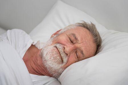 Älterer älterer Mann, der glücklich mit weißer Decke im Schlafzimmer schläft Standard-Bild