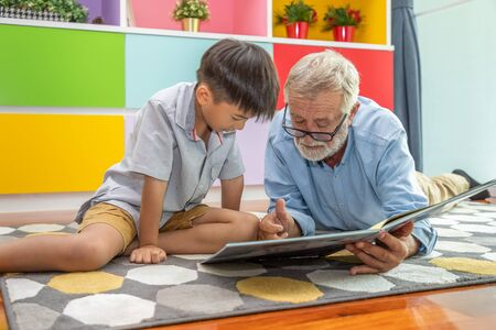 Happy boy grandson reading book with old senior man grandfather at home 写真素材 - 128569254