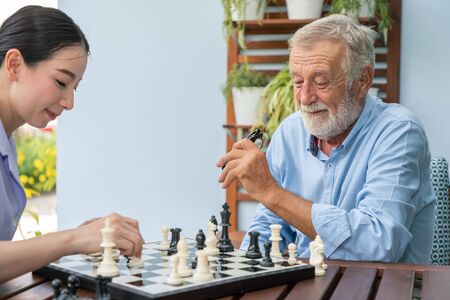 Elderly playing chess with nurse caregiver in nursing home for leisure Stockfoto