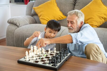 Happy boy grandson playing chess with old senior man grandfather at home 写真素材 - 128569359