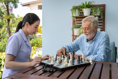 Elderly playing and moving chess with nurse caregiver in nursing home for leisure 版權商用圖片