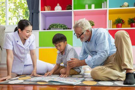 Happy boy reading book with old senior man with nurse at nursery 写真素材 - 128570686