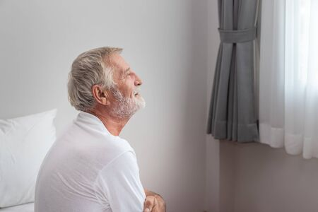 Senior elderly man sitting on bed after waking up in morning