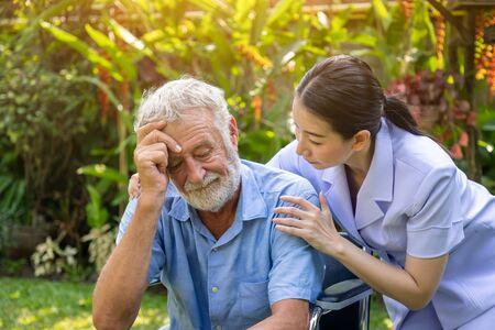 Nurse take care and comfort depressed thoughtful elderly man on wheelchair in garden at nursing home Imagens