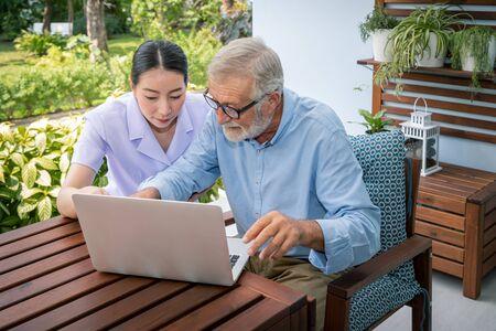 Caregiver assist senoir eldery man using notebook laptop computer connect to Internet Imagens