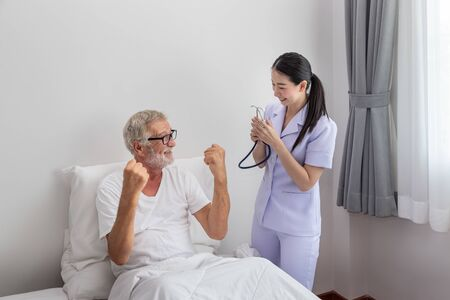 Elderly man healthy rise fist up with happy nurse in bedroom at nursing home thumb up Imagens