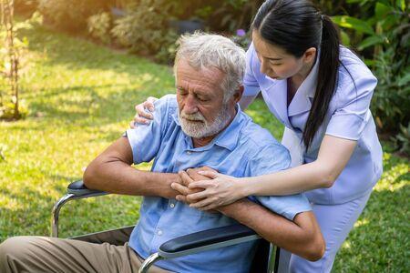 Nurse take care elderly man suffer from chest pain heart attack in garden at nursing home Imagens