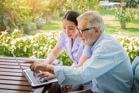 Caregiver assist senoir eldery man typing using notebook laptop computer connect to Internet Imagens