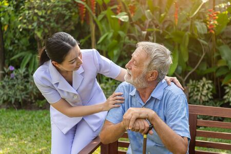 Nurse take care and comfort depressed elderly man in garden at nursing home