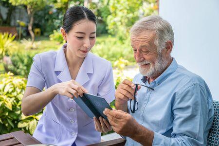 Senior oudere man leest boek met verpleegster tijdens het ontbijt in de tuin bij verpleeghuis