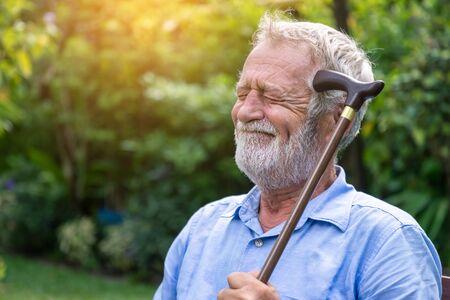 Thoughtful depressed senior old caucasian man holding cane sitting in garden close eye