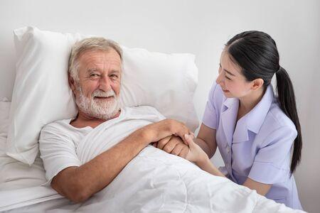 Happy nurse holding elderly man hands with blanket in bedroom at nursing home looking camera