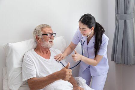 Happy nurse use stethoscope examine elderly man health in bedroom at nursing home thumb up