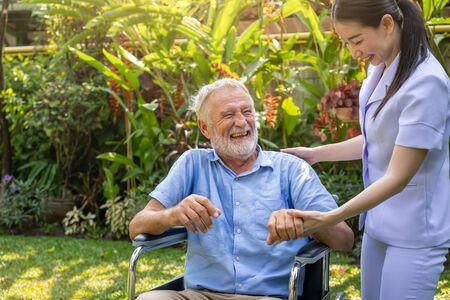 Happy nurse holding laughing elderly man hand on wheelchair in garden at nursing home