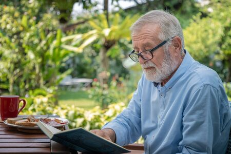 Senior elderly man reading book during breakfast in garden
