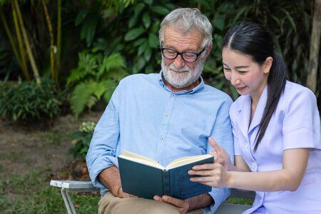 Senior elderly man reading book with nurse in garden at nursing home