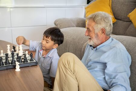 Happy boy grandson playing chess with old senior man grandfather at home