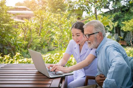 Caregiver assist senoir eldery man typing using notebook laptop computer connect to Internet Stock Photo