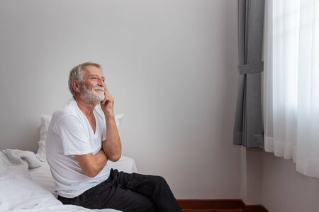 Senior elderly man sitting on bed and thinking after waking up in morning