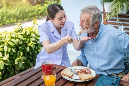 Nurse feeding elderly senior man to eat breakfast at nursing home Stock Photo