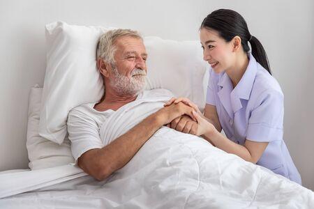 Happy nurse holding elderly man hands with blanket in bedroom at nursing home