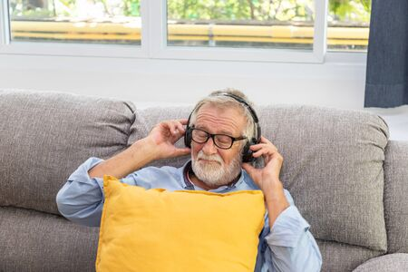 Senior old man eldery enjoy listening to music with headphone on couch sofa