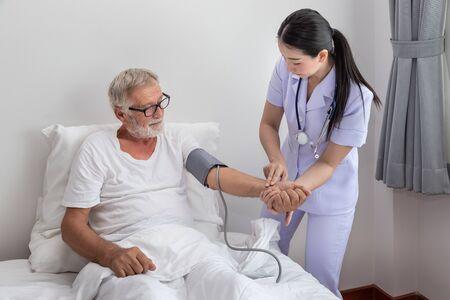 Happy nurse checking and measuring elderly man blood pressure in bedroom at nursing home