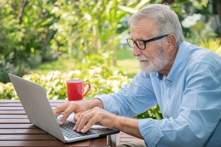 Senior man executive with white hair using typing computer laptop working at home with coffee
