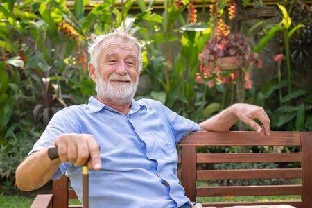 Happy senior old caucasian man holding cane sitting on bench in garden