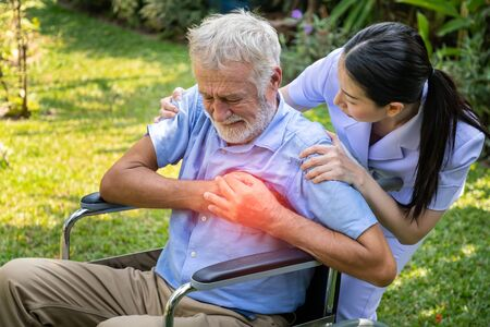 Nurse take care elderly man suffer from chest pain heart attack in garden at nursing home Stock Photo