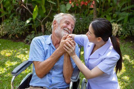 Happy nurse holding elderly man hand on wheelchair in garden at nursing home
