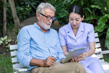 Nurse teach senior elderly man to use tablet in garden at nursing home