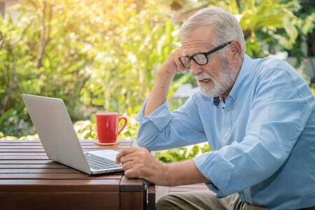 Senior man executive with white hair using computer laptop working at home with coffee Stock Photo