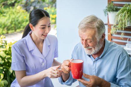 Nurse assist elderly senior man to drink coffee with mug in hand at nursing home Stock Photo