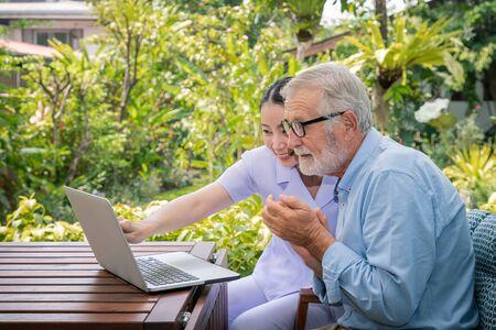 Caregiver assist senoir eldery man using notebook laptop computer connect to Internet Stock Photo
