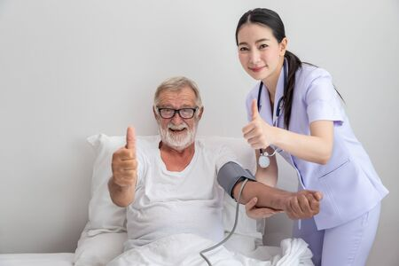 Happy nurse checking and measuring elderly man blood pressure in bedroom at nursing home, thump up, looking camera Imagens