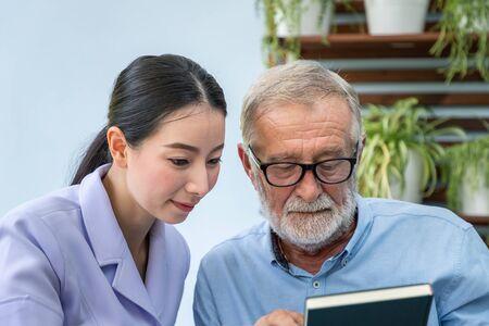 Senior elderly man reading book with nurse in garden Stock Photo