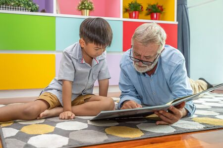 Happy boy grandson reading book with old senior man grandfather at home