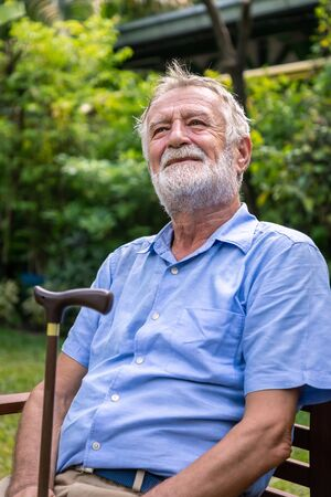 Thoughtful senior old caucasian man holding cane sitting on bench in garden looking at sky