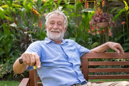 Happy senior old caucasian man holding cane sitting on bench in garden looking at camera