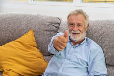 Relax happy senior old man eldery sitting on comfortable sofa in living room Standard-Bild