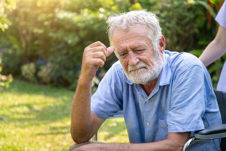 Depressed thoughtful elderly man on wheelchair with nurse in garden at nursing home