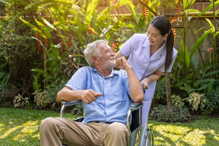 Happy nurse take care elderly man on wheelchair in garden at nursing home with thumb up Imagens