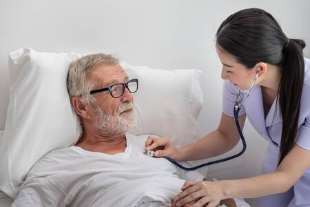 Happy nurse use stethoscope examine elderly man health in bedroom at nursing home