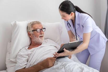 Happy nurse show good health result to elderly man in bedroom at nursing home Stock Photo