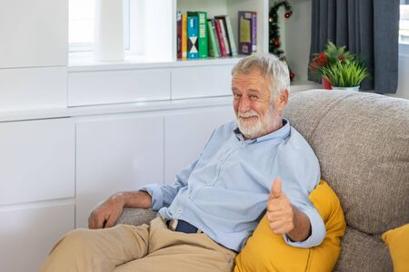 Relax happy senior old man eldery sitting on comfortable sofa in living room thumb up looking camera Stock Photo