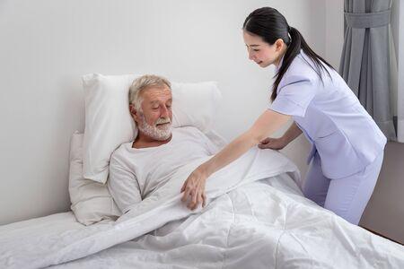 Happy nurse cover elderly man with blanket in bedroom at nursing home