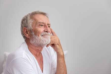 Senior elderly man sitting on bed and try to remember after waking up in morning Stock Photo