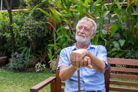 Thoughtful senior old caucasian man holding cane sitting on bench in garden Stock Photo