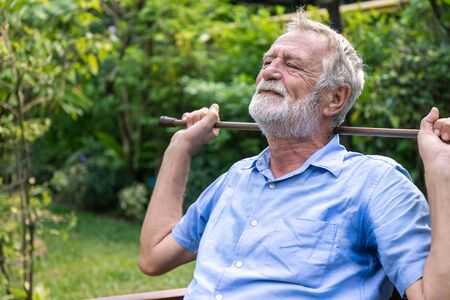 Thoughtful depressed senior old caucasian man holding cane with two hands sitting in garden